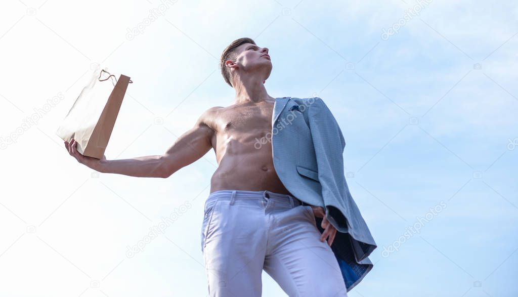 Sales season. Shop assistant concept. Man muscular athlete hold shopping bag sky background. Hot sales and discount. Guy attractive macho carry shopping bag made out of brown paper. Take this package