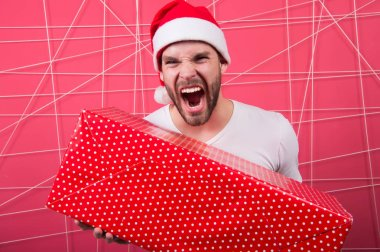 delivery christmas gifts. happy man in santa hat hold christmas present. The morning before Xmas. man enjoy the holiday. Merry Christmas and Happy Holidays. Winter holidays sales