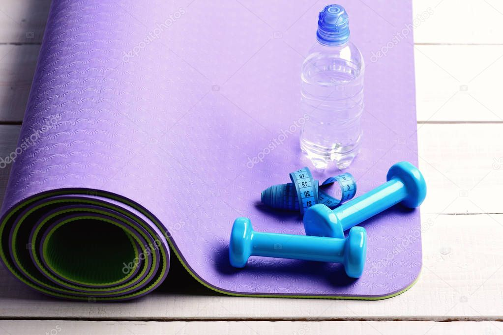 Dumbbells made of blue plastic on light wooden background
