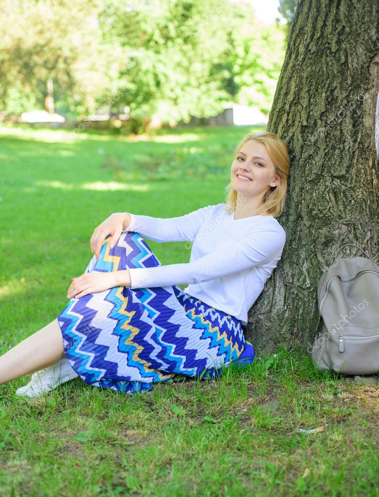 Give yourself break and enjoy leisure. Woman blonde take break relaxing in park. Find peaceful place in park. Girl sit on grass lean on tree trunk relaxing in shadow green nature background