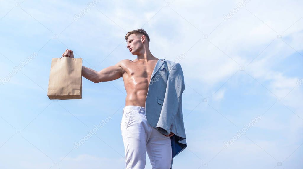 Guy attractive macho carry shopping bag made out of brown paper. Sales season. Eco healthy products. Man muscular athlete hold shopping bag sky background. Hot sales and discount. Take this package