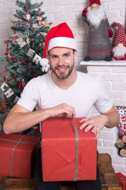 man in santa hat hold christmas present. delivery christmas gifts. online christmas shopping. New year scene with tree and gifts. happy santa man. The morning before Xmas. Office christmas party