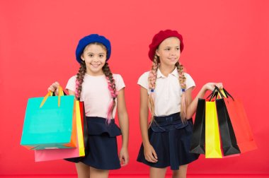 Children pupils satisfied by shopping red background. Obsessed with shopping and clothing malls. Shopaholic concept. Signs you are addicted to shopping. Kids cute schoolgirls hold bunch shopping bags