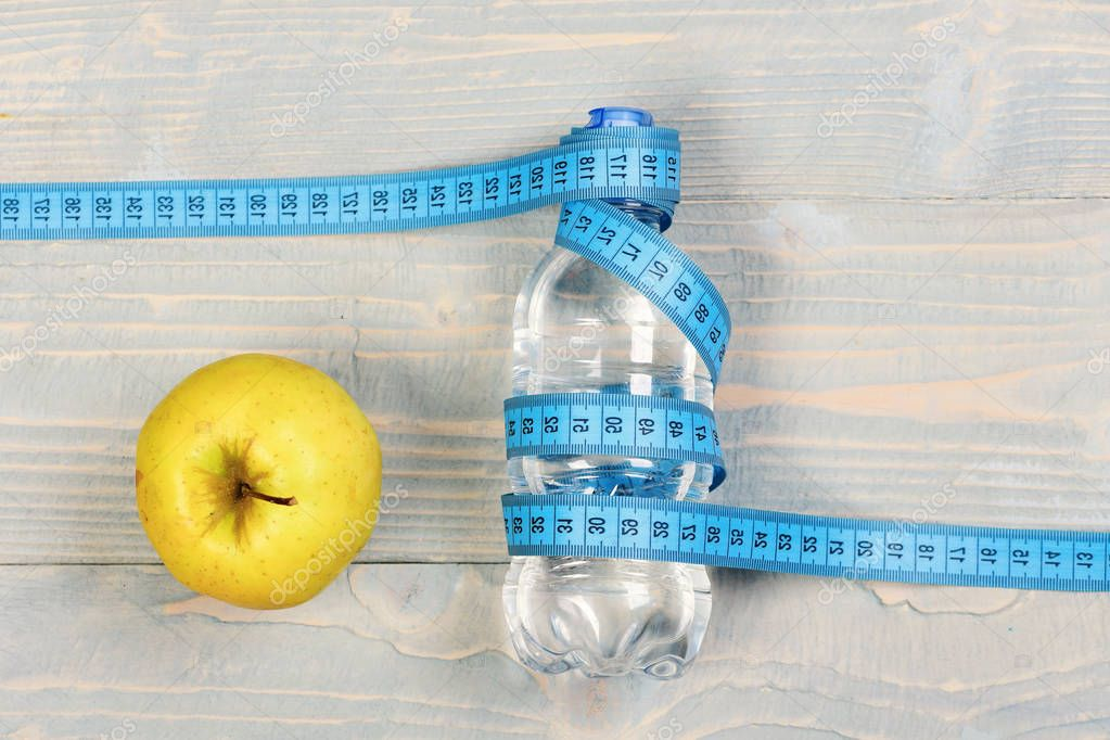 Water, measuring tape and apple, top view