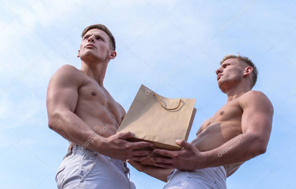 Guys attractive twins carry shopping bag made out of brown paper. Sales season. Men muscular athletes hold shopping bag sky background. Brothers buy eco healthy products. Hot sales and discount