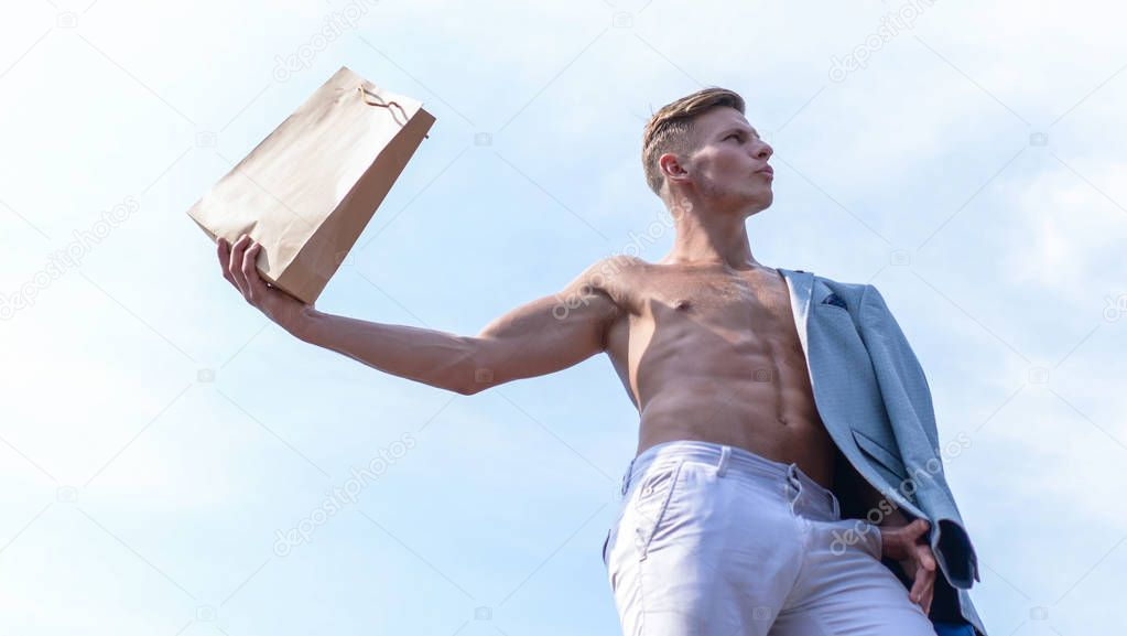 Sales season. Take this package. Shop assistant concept. Man muscular athlete hold shopping bag sky background. Hot sales and discount. Guy attractive macho carry shopping bag made out of brown paper