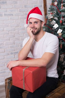 The morning before Xmas. man in santa hat hold christmas present. happy santa man. delivery christmas gifts. online christmas shopping. New year scene with tree and gifts. Christmas Shopping