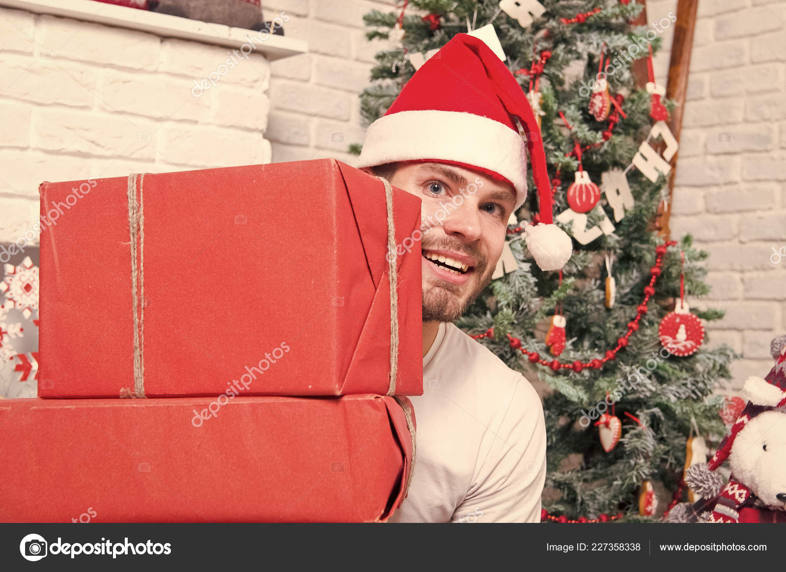 55c11cf38efa7 Macho in red hat smile with wrapped presents. Man santa with boxes at christmas  tree. Boxing day concept. Gift giving and exchange.
