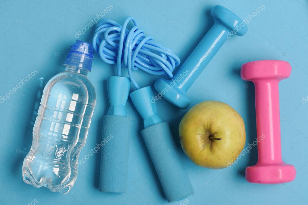Jump rope, apple and barbells next to water bottle