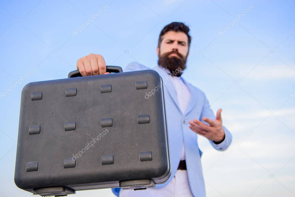 Businessman presenting business case. Entrepreneur offer bribe. Illegal deal business. Hipster bearded face hold briefcase with bribe. Business man formal suit carries briefcase sky background