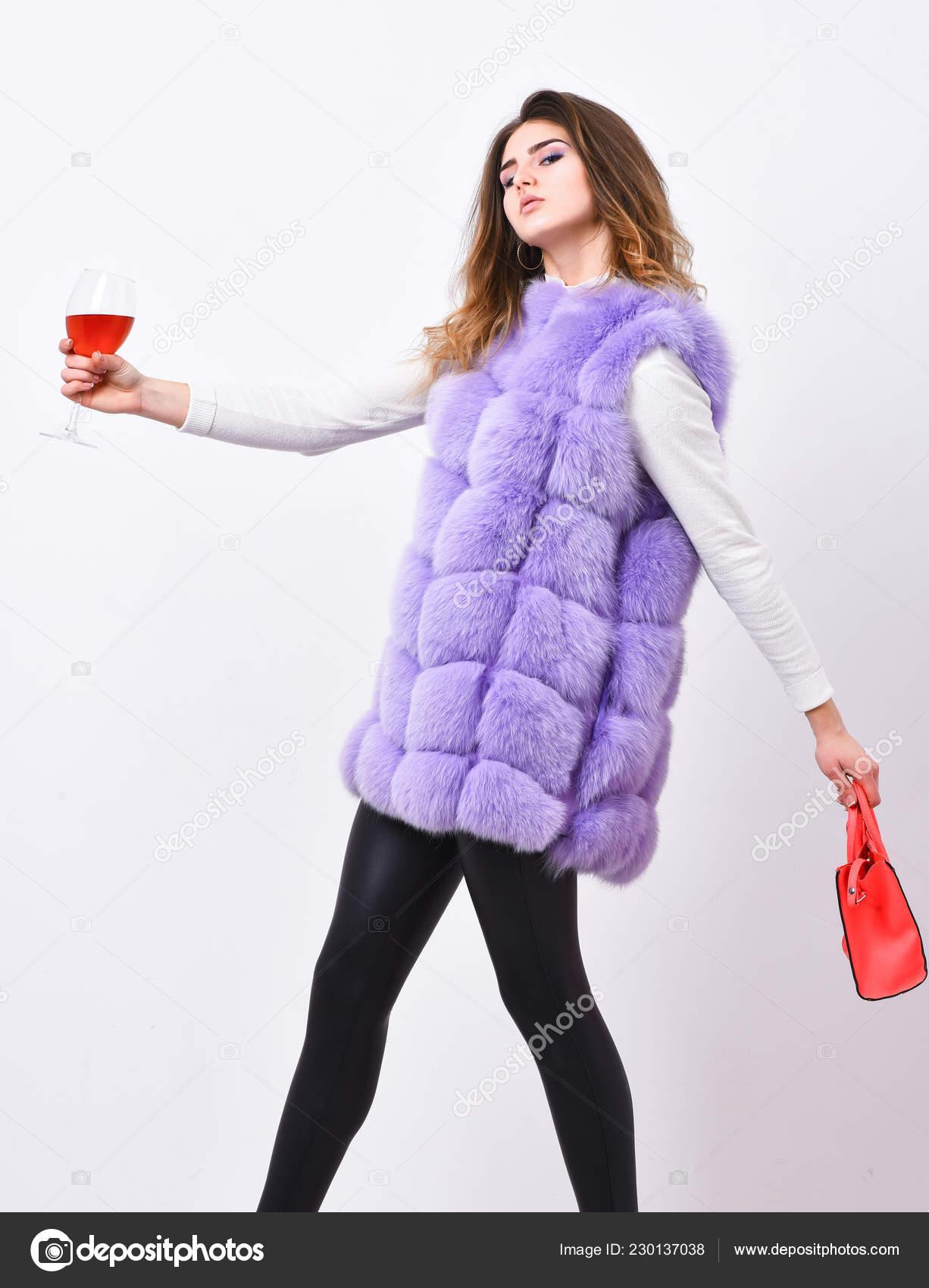 e8dfd95fd8a7 Женщина с сумку держать бокал вина. Девушка носить жилет меховой моды во  время позирует с мешком. Концепция магазина роскоши. Леди любит шоппинг.