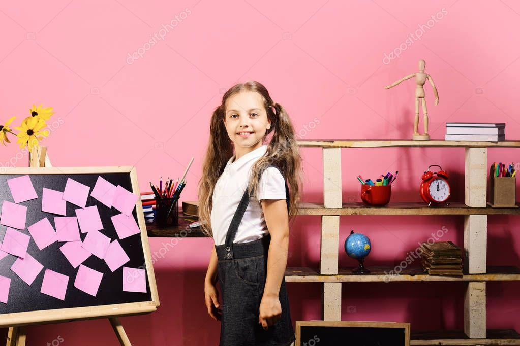 Schoolgirl with proud face in her classroom