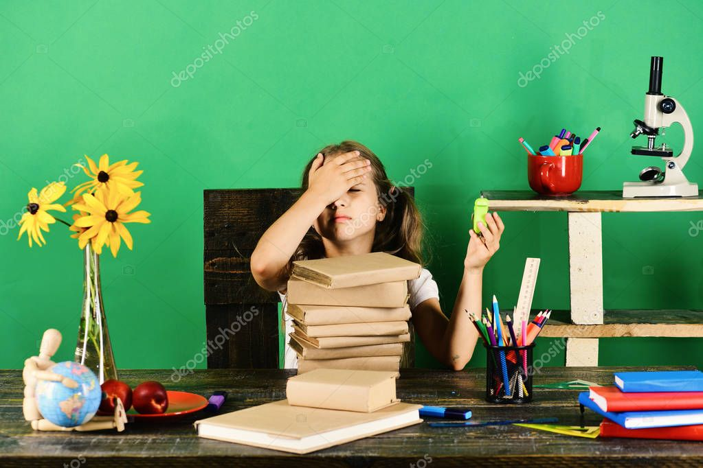 Kid and school supplies on green wall background