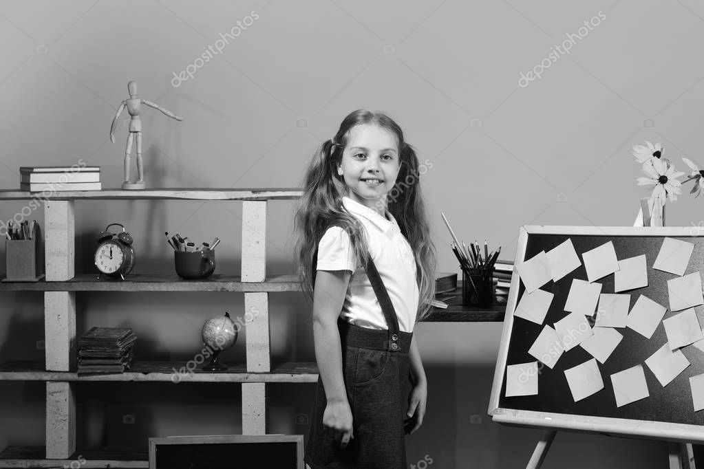 Schoolgirl with proud face in her classroom. Kid and school supplies on pink wall background. Education and back to school concept. Girl stands near bookshelf and blackboard with pink sticky notes