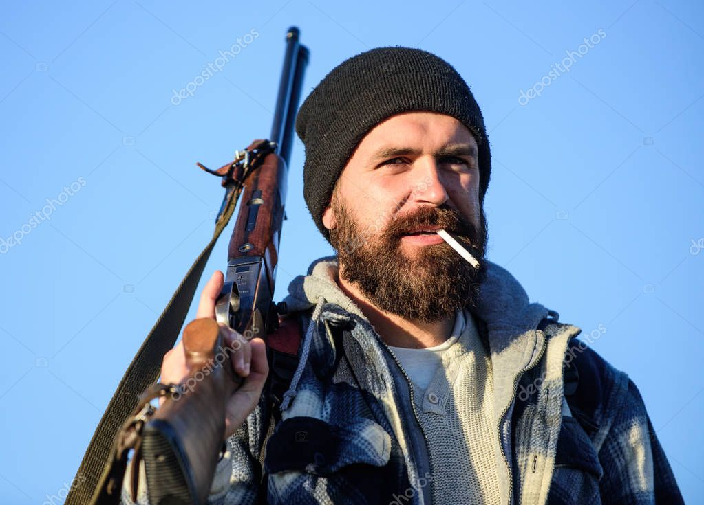 Guy bearded hunter spend leisure hunting and smoking. Hunting masculine hobby concept. Man brutal bearded guy gamekeeper blue sky background. Brutality and masculinity. Hunter with rifle gun close up