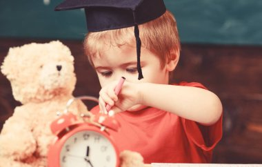 Elementary education concept. First former with toy on desk, close up. Pupil in mortarboard, chalkboard on background. Boy smart, clever, likes studying. Kid studies near alarm clock and teddy bear