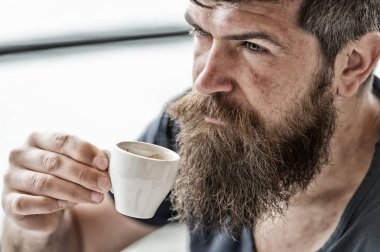 Man with beard and mustache and cup of coffee. Bearded guy relaxing at cafe terrace. Guy relaxing with espresso coffee. Coffee break concept. Hipster drinking coffee outdoor. Enjoy hot drink