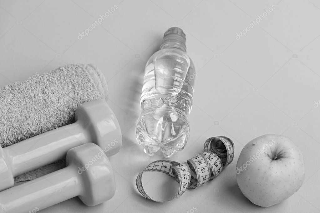 Dumbbells in bright green color, water bottle, measure tape, towel