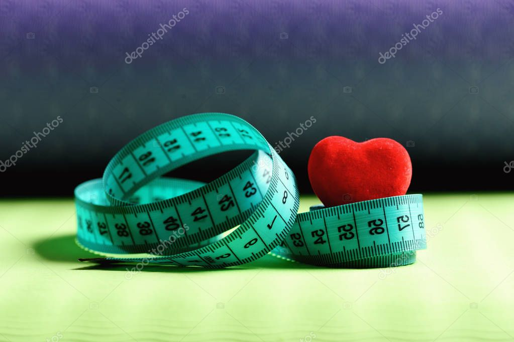 Measuring tape roll in cyan color and soft red heart
