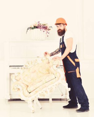Relocating concept. Loader moves armchair for move out. Courier delivers furniture in case of move out, relocation. Man with beard, worker in overalls and helmet lifts up armchair, white background