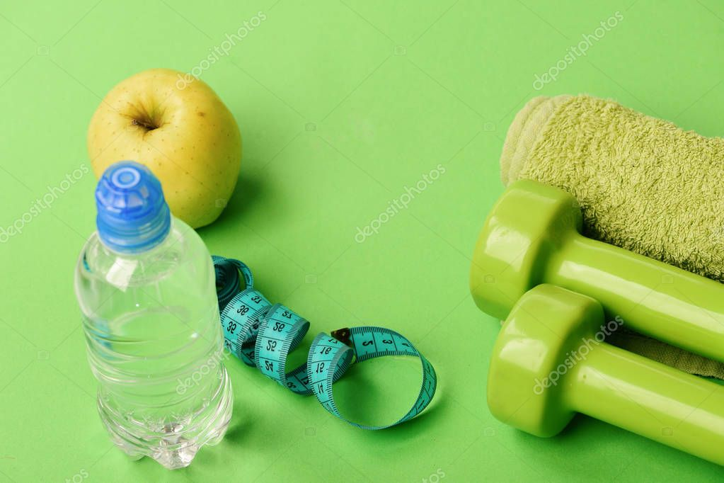 Athletics and weight loss concept. Barbells and towel near juicy green apple. Sports regime equipment. Dumbbells in bright green color, water bottle, measure tape, towel and fruit on green background