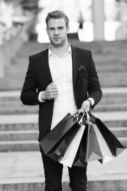 Man formal suit carry shopping bags. Guy carry bunch shopping bags. Profitable deals shopping on black friday. Man hold lot paper bags packages after shopping in mall. Black friday sale concept