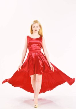 Dress rent service, fashion industry. Woman wears elegant evening red dress, white background. Girl blonde posing in dress. Lady rented fashionable dress for visiting event. Dress rent concept.