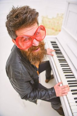 Guy in giant red sunglasses while playing piano. Man, cheerful pianist playing. Comic performer concept. Man in leather jacket sits near piano musical instrument in white interior on background