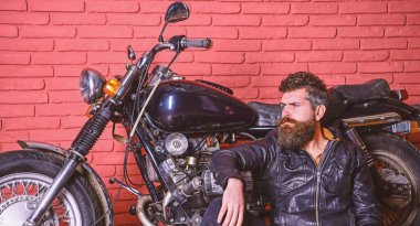 Man with beard, biker in leather jacket near motor bike in garage, brick wall background. Bikers lifestyle concept. Hipster, brutal biker on pensive face in leather jacket sits, leans on motorcycle