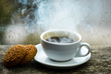 Coffee drink with oat cookies dessert. Enjoying coffee on rainy day. Coffee time on rainy day. Fresh brewed coffee in white cup or mug on windowsill. Wet glass window and cup of hot caffeine beverage