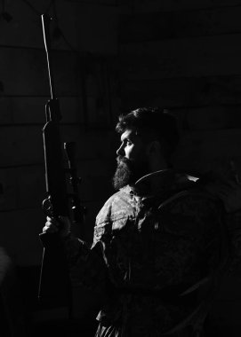 Hunter concept. Hunter brutal with gun and horns of deer, lighted in darkness. Man with beard wears camouflage clothing, dark background. Macho on strict face at gamekeepers house ready for hunting