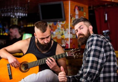 Live music concert. Acoustic performance in pub. Hipster brutal bearded with friend in pub. Cheerful friends sing song guitar music. Relaxation in pub. Friends relaxing in pub. Man play guitar in pub