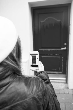 woman take a picture of red door on smartphone outside. digital age and facade design. photo of door on phone. navigation and locations. red point. this would be my home. i like it.