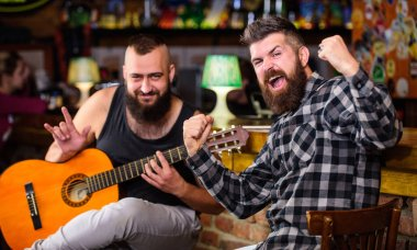 Friends relaxing in pub. Live music concert. Man play guitar in pub. Acoustic performance in pub. Hipster brutal bearded with friend in pub. Cheerful friends sing song guitar music. Relaxation in pu