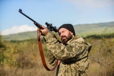Aiming skills. On my target. Bearded hunter spend leisure hunting. Hunting optics equipment for professionals. Brutal masculine hobby. Man aiming target nature background. Hunter hold rifle aiming