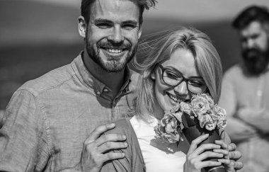 Lovers hugs outdoor flirt romance relations. Couple in love dating while jealous bearded man watching wife cheating him with lover. Infidelity concept. Couple romantic date lovers bouquet flowers