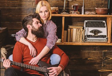 Lady and man with beard on dreamy faces hugs and plays guitar. Couple in wooden vintage interior enjoy guitar music. Romantic evening concept. Couple in love spend romantic evening in warm atmosphere