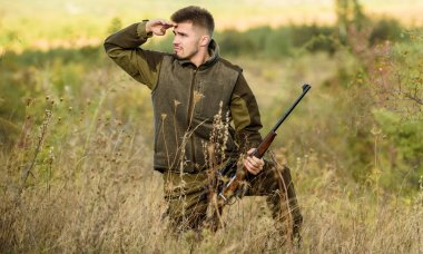 Hunting permit. Bearded hunter spend leisure hunting. Hunter hold rifle. Focus and concentration of experienced hunter. Hunting and trapping seasons. Man brutal gamekeeper nature background