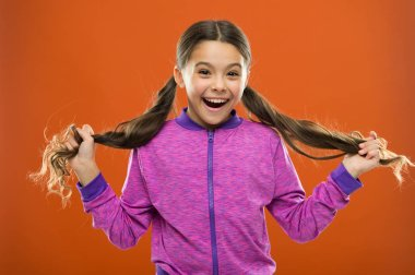 childhood happiness. Family. Kid fashion and sportswear. Happy little girl with long hair. childrens day. Portrait of happy little child. Small girl child. Hairdresser for kids. Little daydreamer