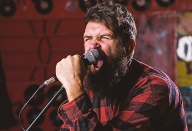 Musician with beard and mustache singing song in karaoke. Rock star concept. Man with tense face holds microphone, singing song, karaoke club background. Guy likes to sing in aggressive manner