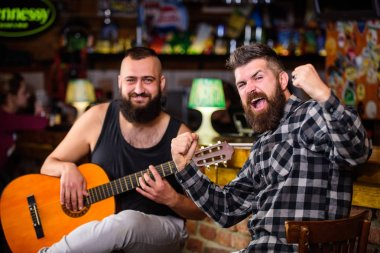 Live music concert. Man play guitar in pub. Acoustic performance in pub. Hipster brutal bearded with friend in pub. Cheerful friends sing song guitar music.