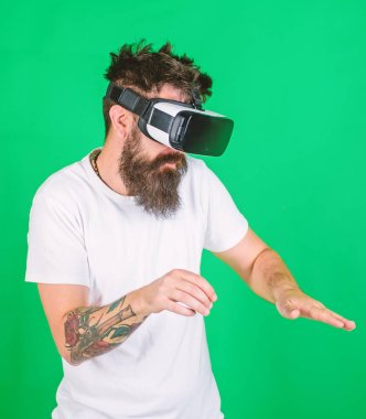 Man with beard in VR glasses, green background. Hipster on busy face use modern technologies for entertainment or education. VR musician concept. Guy DJ with VR glasses play music with mixing console