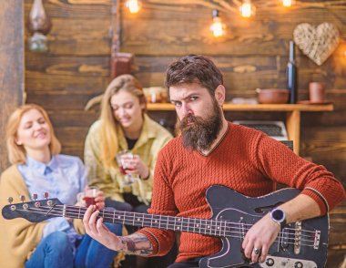 Rock musician with long beard and tattooed arm playing guitar. Bearded man with stern eyes looking at camera. Guitarist composing new song. Man with hipster beard entertaining his wife and daughter