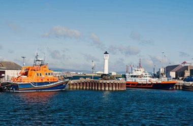 Kirkwal, United Kingdom - February 19, 2010: sea harbor with ships and lighthouse on blue sky. Water transport and transportation. Travelling by sea. Summer vacation on island. Wanderlust and journey
