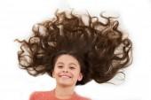 Péče, která dává zdravé krásné vlasy. Roztomilé dítě dívka s dlouhými kudrnatými vlasy izolované na bílém. Vlasy masky recept. Kadeřnictví salon koncept. Maska pro dlouhé vlasy. Kosmetické ošetření pro poškozené vlasy