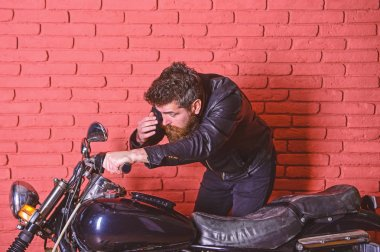 Masculinity concept. Man with beard, biker in leather jacket near motor bike in garage, brick wall background. Hipster, brutal biker on serious face in leather jacket looks into mirror of motorcycle
