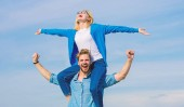 Photo Soulmates enjoy freedom together. Couple in love enjoy freedom outdoor sunny day. Couple happy date having fun together. Freedom concept. Man carries girlfriend on shoulders, sky background