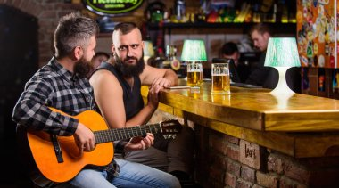 Man play guitar in bar. Cheerful friends relax with guitar music. Friday relaxation in bar. Friends relaxing in bar or pub. Real men leisure. Hipster brutal bearded spend leisure with friend in bar
