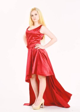 Dress rent service, fashion industry. Woman wears elegant evening red dress, white background. Dress rent concept. Girl blonde posing in dress. Lady rented fashionable dress for visiting event.
