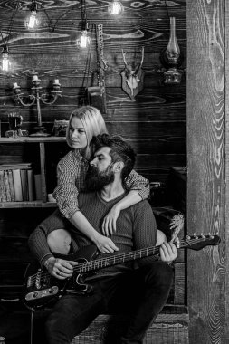 Couple in wooden vintage interior enjoy guitar music. Lady and man with beard on dreamy faces hugs and plays guitar. Couple in love spend romantic evening in warm atmosphere. Romantic evening concept